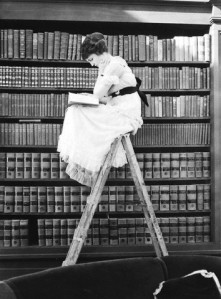 [ woman reading on top of ladder ] 1920